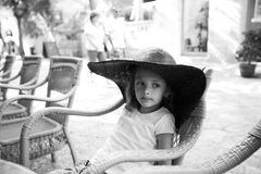 Cute girl in oudoor cafe. Portrait of a cute little girl in a wide hat sitting on a chair in outdoor cafe Royalty Free Stock Images