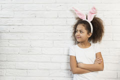 Cute girl over a brick wall with bunny ears Stock Photography