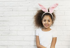 Cute girl over a brick wall with bunny ears Royalty Free Stock Photos