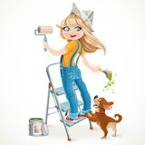 Cute girl in overalls standing on a stepladder with a paint roll Royalty Free Stock Photography