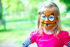 Cute girl with painted face playing outdoors Royalty Free Stock Photos