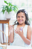Cute girl painting easter eggs Stock Photos