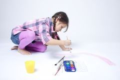 Cute girl painting rainbow. On white background Royalty Free Stock Images
