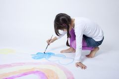 Cute girl painting rainbow. On white background Royalty Free Stock Photo