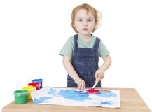Cute girl painting on small desk looking to camera royalty free stock image