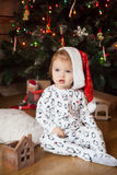 Cute girl in pajamas and christmas hat Royalty Free Stock Photography