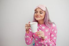 Cute girl in pajamas and sleep mask inhales the aroma of coffee. Happy young woman drink morning coffee. Beautiful girl in pink pajamas and mask for sleep royalty free stock photo