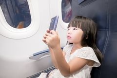 Girl paly phone. Cute girl paly phone in the airplane Stock Photos