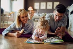 Cute girl with parents play with puzzle indoor royalty free stock image