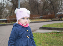 Cute girl in park. Sad little girl walking under the rain Royalty Free Stock Image