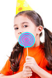 Cute girl in party hat with colored candy. Stock Photos