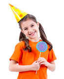 Cute girl in party hat with colored candy. Royalty Free Stock Photos