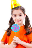 Cute girl in party hat with colored candy. Stock Photography