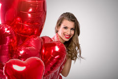 Cute girl peeking behind Valentine's Day balloons Royalty Free Stock Photography