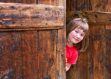 Cute girl peeping behind an old wooden door. Cute girl dressed in red peeping behind an old wooden door royalty free stock photos