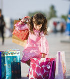 Cute girl picking up shopping bags Stock Photo