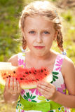 Cute girl with pigtails eating a watermelon Stock Image