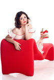 Cute girl in pin-up pose on red couch Royalty Free Stock Photo
