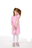 Cute girl in pink dress. Shrugging her shoulders Stock Image