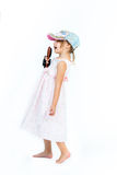 Cute girl in pink dress and fashion cap singing to Stock Photography