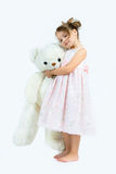 Cute girl in pink dress hugs big white bear on light background. Child and toy Stock Images