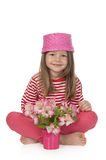 Cute girl with pink flowers. Cute smiling girl at the age of five with pink flowers sitting on the floor and looking at the camera on white background Royalty Free Stock Images