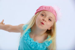 Cute girl in pink hat. Portrait of cute young blond girl in party dress with pink woollen hat; white studio background Stock Images
