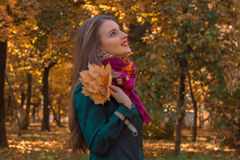 Cute girl in pink scarf stands sideways in the Park and keeps the leaves in hand Royalty Free Stock Photos
