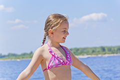 Cute girl in pink swimsuit stock photos
