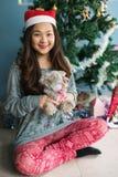 Cute girl play teddy bear near xmas tree. Asian Chinese happy woman with santa claus hat hold teddy bear doll near Xmas tree. Cute girl celebrate Christmas royalty free stock image
