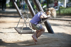 Cute girl on the playground swinging Royalty Free Stock Images
