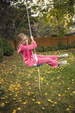 Cute girl playing on a backyard rope swing outdoors Stock Photos