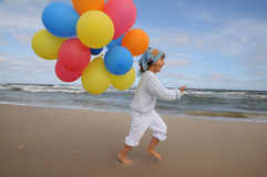 Cute girl playing with balloons on the beach. Little girl playing with balloons on the beach Royalty Free Stock Photos
