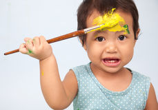 Cute girl playing with brush and paint. Toddler playing with brush and paint Stock Photos