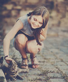Cute girl playing with cat. Cute young girl with a smile playing with cat at street Royalty Free Stock Images