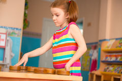 Cute girl playing checkers at daycare Royalty Free Stock Images