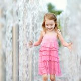 Cute girl playing with a city fountain Royalty Free Stock Images