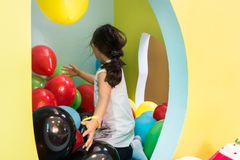 Cute girl playing with colorful balloons during playtime at the kindergarten Stock Image