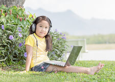 Cute girl playing computer with headphone at prk. Cute girl playing computer with headphone on nature background Royalty Free Stock Image