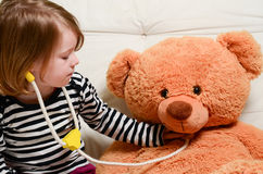 Cute girl playing doctor with plush toy bear Stock Images