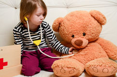 Cute girl playing doctor with plush toy bear Stock Photos