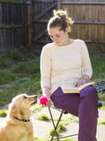 Cute girl playing with dog outdoor Royalty Free Stock Image