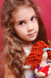 Cute girl playing with doll Stock Images