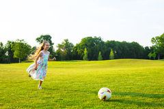 Cute girl is playing football. Royalty Free Stock Images