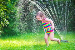 Cute girl playing with garden sprinkler. Funny laughing little girl in a colorful swimming suit running though garden sprinkler playing with water splashes stock photos