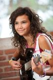 Cute girl playing the guitar. Stock Photos