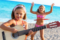 Cute girl playing guitar with friend dancing in background. Stock Photo