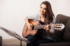 Cute girl playing guitar at home Stock Photos