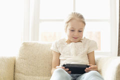 Cute girl playing hand-held video game at home Royalty Free Stock Photo