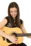 Cute girl playing her acoustic guitar looking down Royalty Free Stock Images